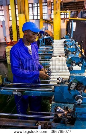 African Factory Worker On A Copwinder Weft Assembly Line Loom