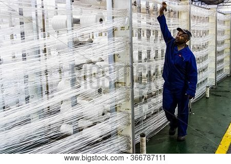 Johannesburg, South Africa - October 16, 2012: African Worker Checking Cotton Thread Lines For A Cop