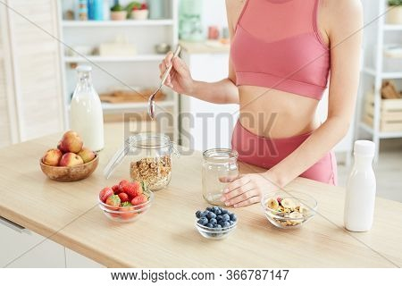 Close Up Of Fit Young Woman Opening Granola Jar While Cooking Healthy Snack In Kitchen Interior, Cop