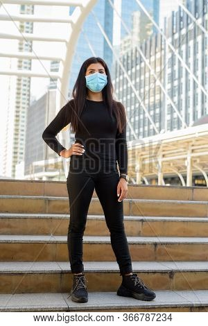 Full Body Shot Of Young Indian Woman With Mask Standing On Stairs At The Skywalk Bridge
