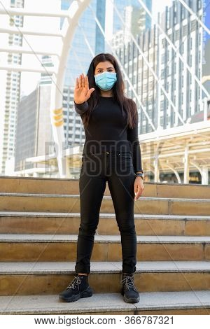 Full Body Shot Of Young Indian Woman With Mask Showing Stop Gesture By The Stairs In The City
