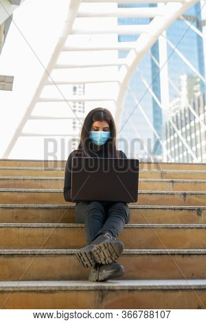 Full Body Shot Of Young Indian Woman With Mask Using Laptop At Skywalk Bridge In The City