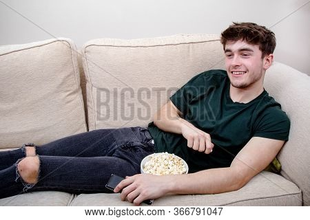 A Young Adult Man Laying On A Sofa Watching Tv And Eating Snacks