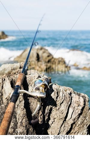 Spinning for fishing on the rocks by the sea