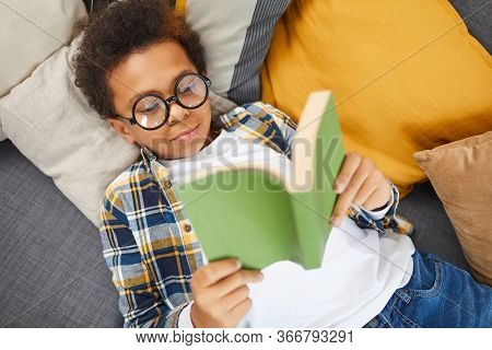 Above View Portrait Of Cute African Boy Wearing Big Glasses Reading Book While Lying On Couch, Homes