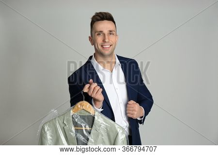 Man Holding Hanger With Jacket In Plastic Bag On Light Grey Background. Dry-cleaning Service