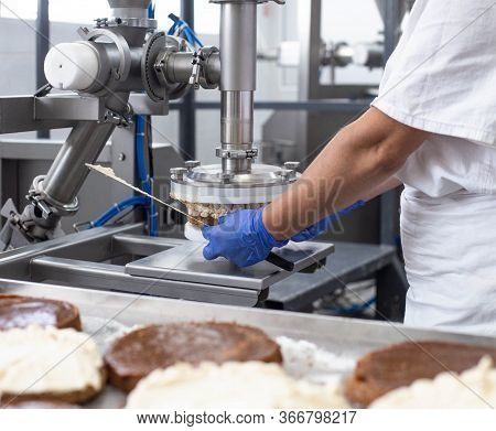 The Pastry Chef Makes Cake Using Modern Equipment For The Production Of Cakes. Line For Spreading Cr