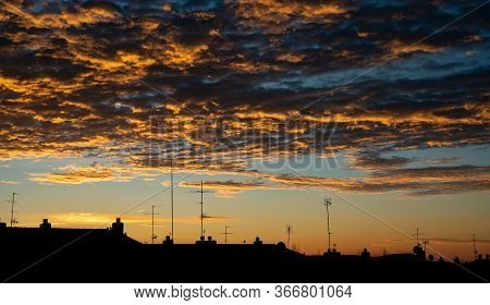 High Contrast Clouds During Sunrise With Buildings Silhouette Spiritual Concept