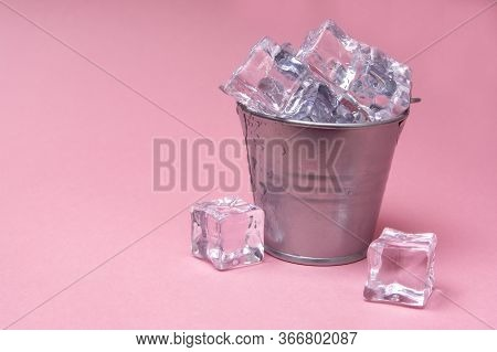 Ice Cubes. Bucket With Ice Cubes. Isolated On A Pink Background / Copy Space For Text