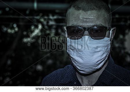 Man Wearing A White Cloth Face Mask And Black Sunglasses In A Strange Sad Portrait, Green Teal Tint