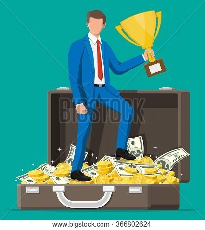 Successful Businessman In Briefcase With Dollar And Coins Holding Trophy, Celebrates His Victory. Bu