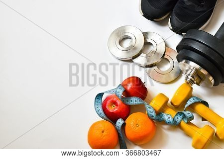 Sports Equipment For Practicing Sports Dumbbells, Measuring Tape, Fruits, Sneakers On A White Backgr