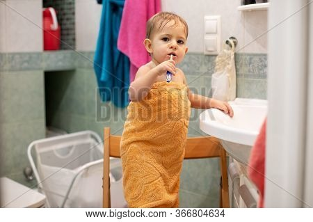 Little Cute Baby Is Standing On A Chair In The Bathroom Wrapped In An Orange Towel With A Toothbrush