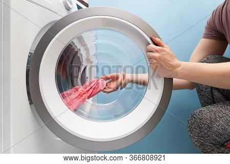 Girl Takes Out The Laundry From The Washing Machine. Woman Puts Clothes In A Washing Machine