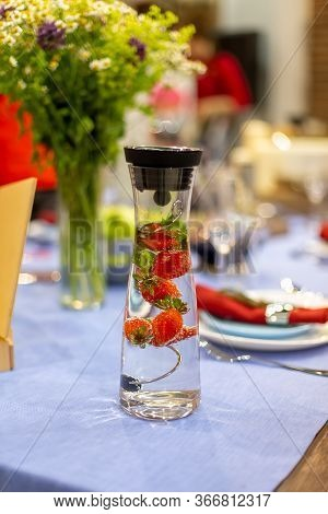 A Carafe Filled With Water And Strawberries Stands On A Served Blue Table. Close Up, Soft Focus. Ser