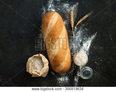 British White Bloomer Or European Sourdough Baton Loaf Bread On Black Background. Fresh Loaf Bread A