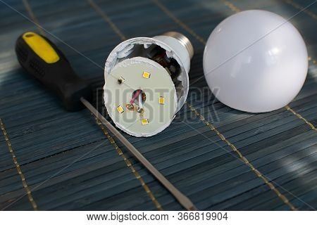 Faulty, Disassembled Led Household Lamp With A Burnt Led Element Is On The Table Next To The Screwdr