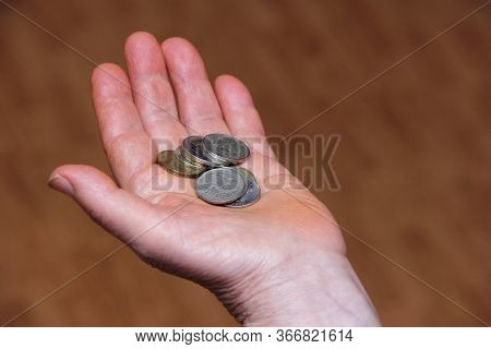 Russian Rubles In Coins In The Hand Of An Elderly Person. Below The Breadline. Pension Reform Concep