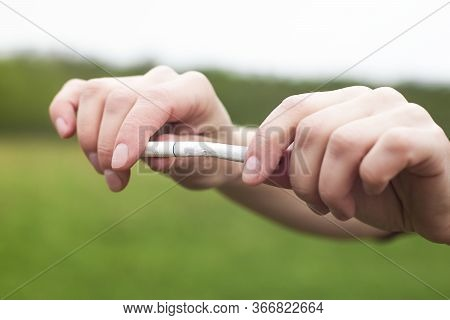 Broken Cigarette In Human Hands, Person Man Or Woman Is Going To Break Apart A Cigarette On Green Na