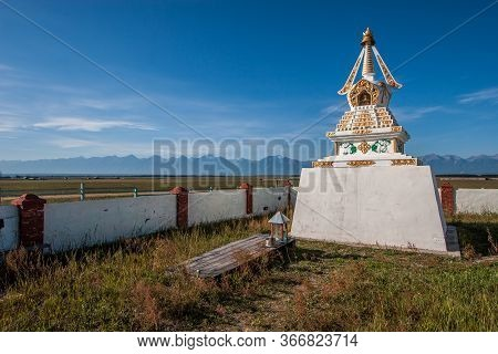 A Buddhist Stupa Stands In A Field Against A Blue Sky. White Tibetan Stupa With Decorations. Mountai