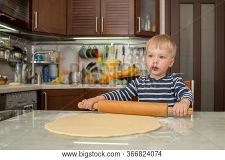 Little Cute Blond Boy In Kitchen Prepares Pie Dough By Rolling It Out On Table With Rolling Pin