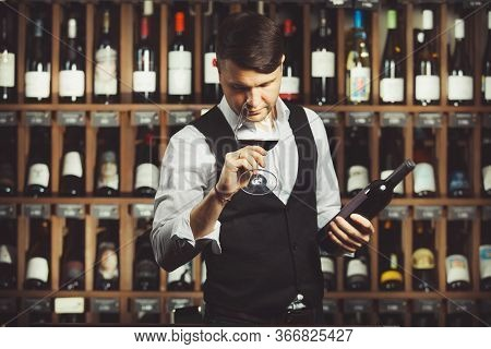 Person Holding Bottle And Glass Of Fine Red Wine, Sniffing Its Fragrance To Denote Its Age, Cellar W