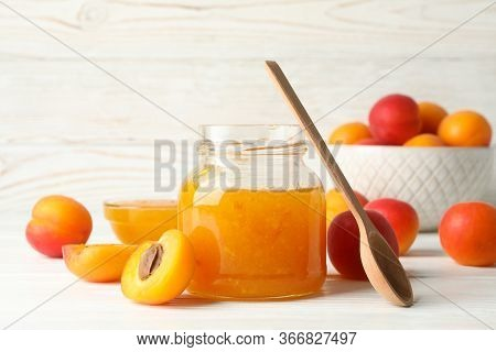 Composition With Tasty Apricots And Jam On White Wooden Table