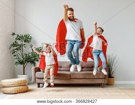 Full Body Of Cheerful Father With Two Children In Casual Clothes And Red Superhero Cloaks Jumping Fr