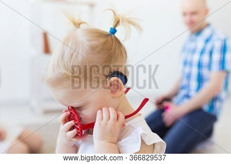 Hearing Aid In Baby Girls Ear. Toddler Child Wearing A Hearing Aid At Home. Disabled Child, Disabili