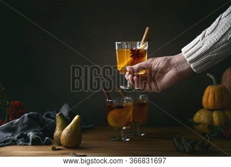 Young Man Holding A Glass Full Of Pear Cider, Front View, Dark Fall Concept With Copy Space