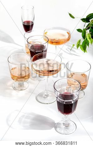 Rose Wine Assortment, Front View Of Various Wine Glasses Full Of Rose And Red Wine, Standing On A Wh