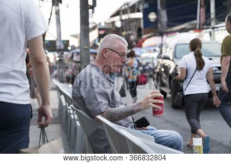 Thailand, Phuket, April 15, 2020: A White-haired European Man Is Sitting On His Face And Drinking Be