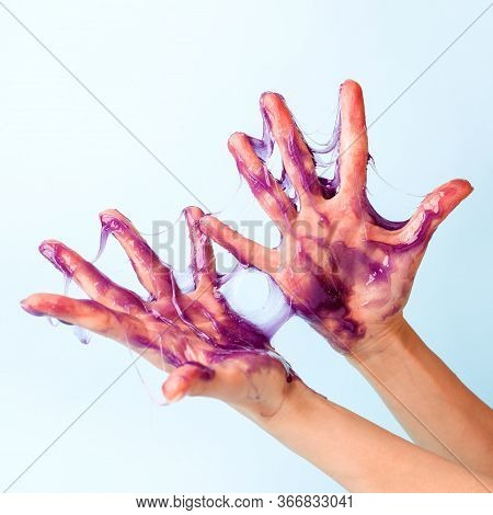Young Girl Hands With Sticky Purple Slime On Blue Background, Liquid Wax For Depilation, Conceptual