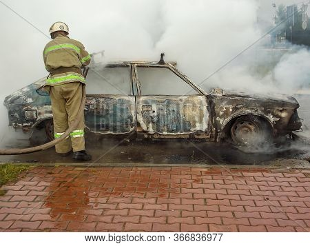Firefighter Puts Out A Burning Car. From The Vehicle There Was Only A Charred Body. Arson Or Sabotag
