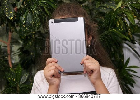 The Girl Holds A Digital Tablet In Front Of Her Face. To Spoil Your Eyesight. Harm To The View From