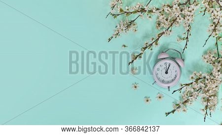 Pink Alarm Clock And Delicate Little White Flowers On Blue Background. Top View. Time For Love And G