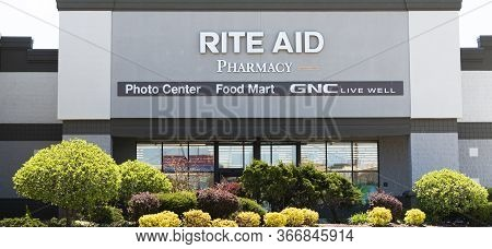 Bay Shore, New York, Usa - 25 April 2020: The Front Of A Rite Aid Pharmacy With Bushes, Shrubs And T
