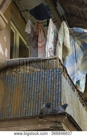 Two Pigeons Are Sitting On The Old Balcony Of An Apartment Building In A Poor Provincial Area Of The