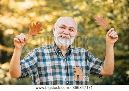 Happy Senior Man. Portrait Of Senior Man In The Autumn Park. Senior Man Strolling In A Park In Autum