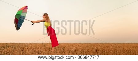 Side View Of Strong Female With Colorful Umbrella Fighting Wind Against Sundown Sky While Standing I