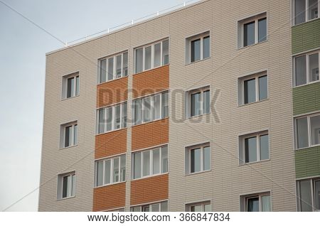 Modern New Building With A Lot Of Flats. There Are Windows And Balconies. Light Blue Sky Above