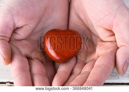 A Close Up Image Of A Hand Holding A Heart Shaped Red Jasper Healing Crystal.