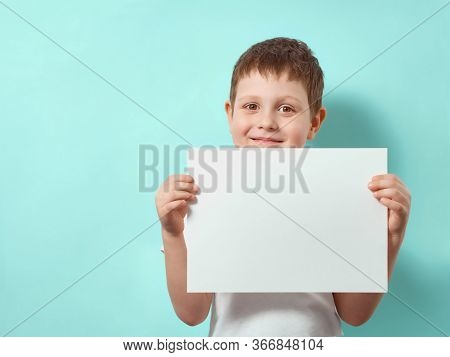 Four-year-old Boy Smiles And Holds Blank White Paper Sheet. Happy Child On Blue Background With Copy