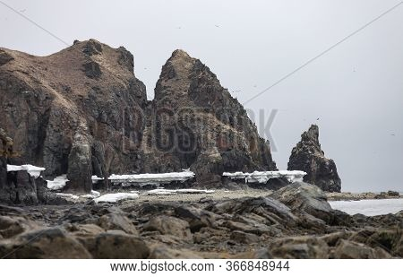 Rocky Coast Of The Sea Of Okhotsk On A Cloudy Foggy Spring Day. Cliffs, Rocks And Coastal Ice On The