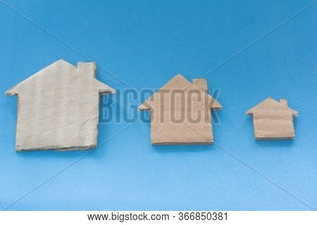 Different Size Of Houses Arranged In Row On Blue Background. Three Differently Sized Cardboard Model