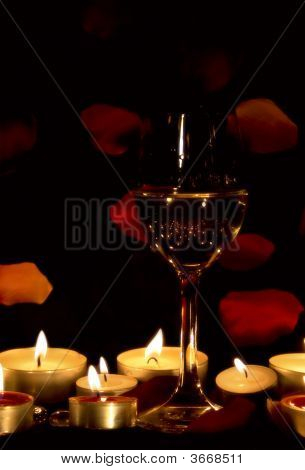 Glas Wein und Kerzen mit BlumenblГ ¤ tter der Rosen