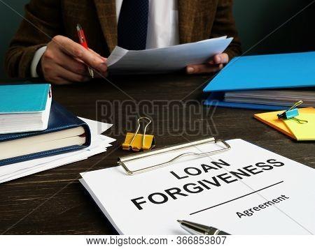 Loan Forgiveness Form And Man Checks Documents.