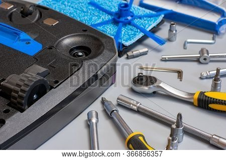 Robot Vacuum Cleaner. Vacuum Cleaner Robot Repair On Grey Background With Tools. Vacuum Cleaner Serv