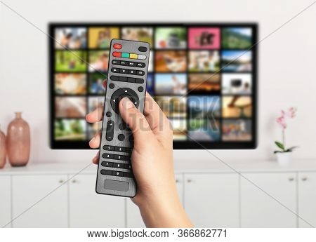 Streaming Video Services. Woman Using Remote Control To Change Channels On Tv, Closeup