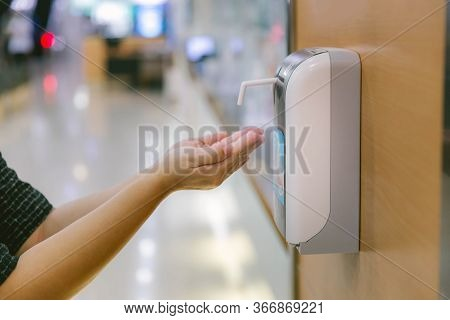 Hands Under The Automatic Alcohol Dispenser. Infection And Hospitably Concept. Save And Protect Dise